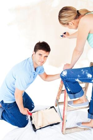 paintrush: Beautiful caucasian couple painting a room