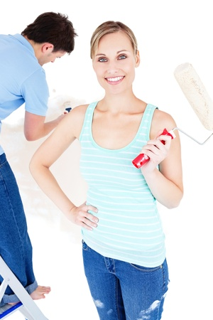 Merry young couple painting a room Stock Photo - 10163736
