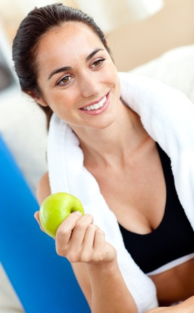 Smiling woman eating an apple on the sofa after working out in the living-room Stock Photo - 10163377