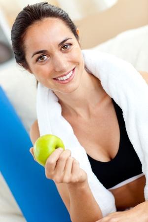 muskeltraining: Strahlende Frau isst einen Apfel auf dem Sofa nach dem Training im Wohnzimmer Lizenzfreie Bilder