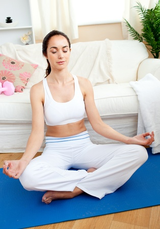 yoga pillows: Relaxed woman doing yoga sitting in her living-room