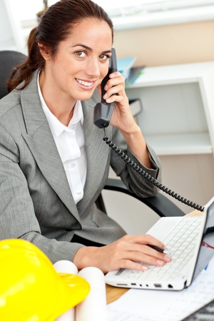 Smiling female architect talking on phone and using her laptop in her office photo