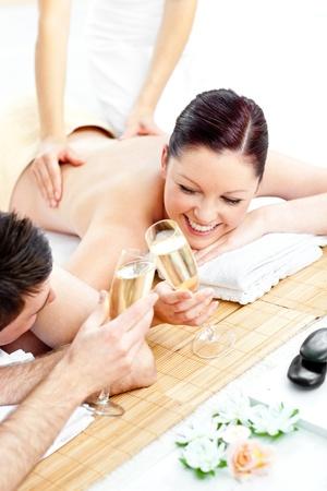 homme massage: Amoureux de la jeune couple boire le champagne allong� sur une table de massage
