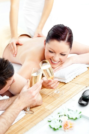 Loving young couple drinking champagne lying on a massage table photo
