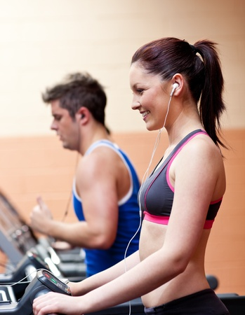 musculation: Young athletes exercising on a running machine with earphones