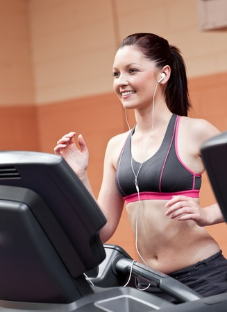 musculation: Smiling athletic woman training on a running machine with earphones