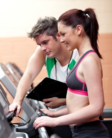 Beautiful athletic woman standing on a running machine with her personal coach Stock Photo - 10164079
