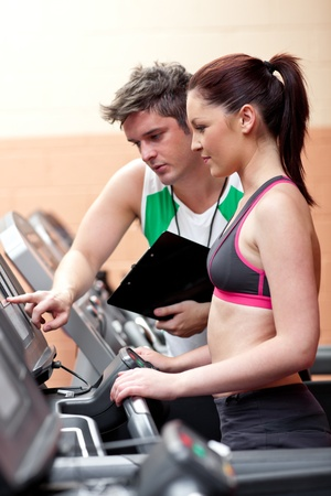 musculation: Beautiful female athlete standing on a running machine talking with her personal coach