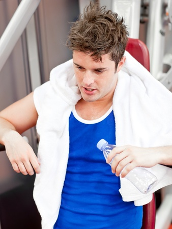 musculation: Tired man with a towel and a bottle of water sitting on a bench press Stock Photo