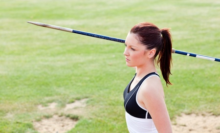 javelin: Concentrated female athlete ready to throw javelin