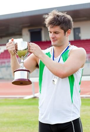 muskeltraining: Sportliche Mann, eine Tasse und eine Medaille hält