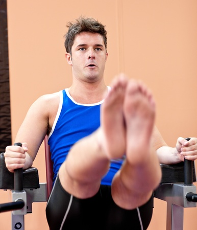 Muscular young man exercising photo