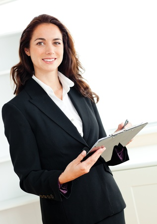 Glowing young businesswoman taking notes on her clipboard photo