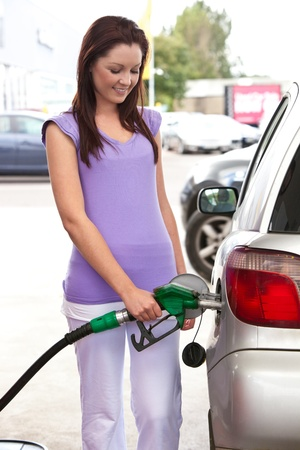 benzine: Pretty caucasian woman refueling her car Stock Photo