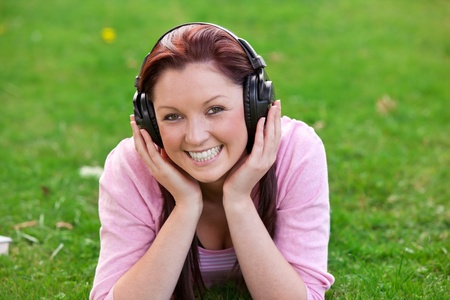Delighted young woman listening to music with headphones lying on the grass photo