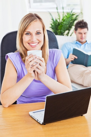 Beautiful woman drinking coffee and using laptop while boyfriend is reading a book Stock Photo - 10175895