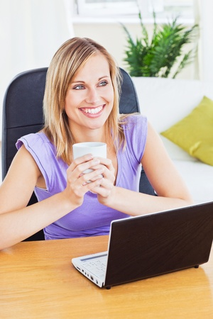 Smiling woman holding a glass of water behind her laptop photo