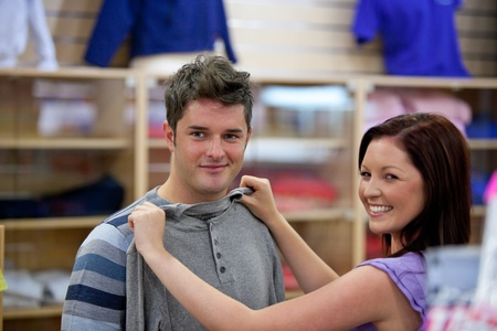 trying on: Cute woman choosing clothes for her boyfriend in a shop Stock Photo