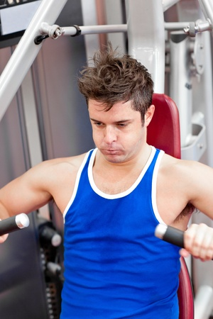 Young man putting a lot of effort sitting on a bench press Stock Photo - 10175841