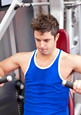 musculation: Gorgeous man working hard on a bench press in a fitness centre