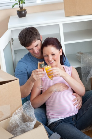 Cheerful couple celebrating pregnancy and removal with champagne sitting on the floor photo