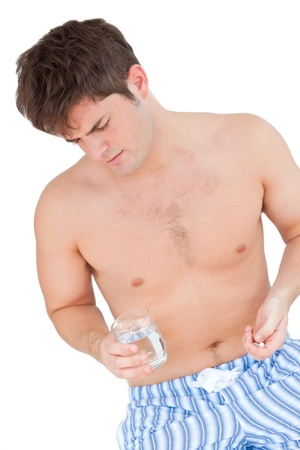 Bare-chested man in pajamas holding pills and a glass of water photo
