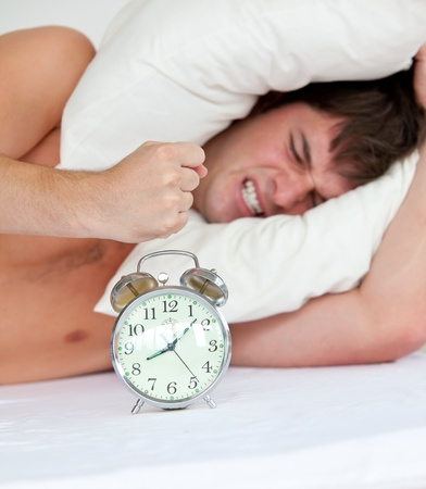 Angry man stressed by his alarm clock lying on his bed photo