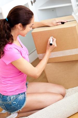 Happy hispanic woman writing on a cardboard photo