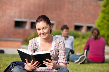 Delighted female student reading a book sitting on grass photo