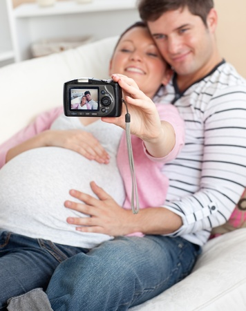 Close-up of a joyful pregnant woman and her husband taking pictures of themselves on a sofa photo