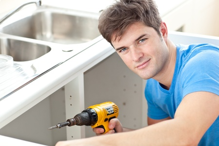 Handsome man holding a drill repairing a kitchen sink photo