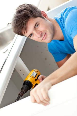 Charismatic man repairing his sink and holding a drill in the kitchen photo