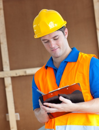 Handsome worker with hardhat taking notes on his clipboard photo