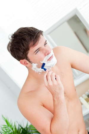Attractive caucasian man shaving in the bathroom Stock Photo - 10169895