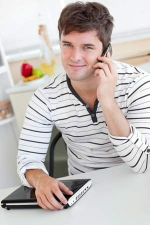 Attractive man talking on phone using his laptop in the kitchen photo