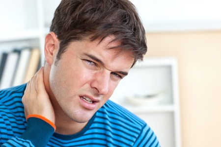 head pain: Dejected caucasian man having a neckhache in the living-room