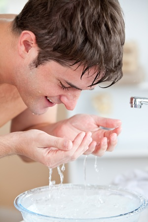 Smiling caucasian man spraying water on his face after shaving in the bathroom Stock Photo - 10164537