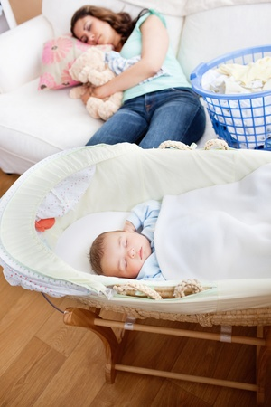 Young mother sleeping on the sofa while her baby is sleeping in his cradle in the living-room photo