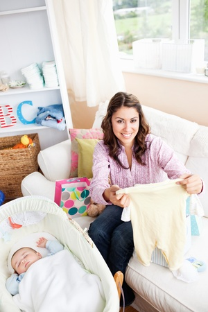 Joyful woman sitting on the sofa with bags reading a card while her baby is sleeping in his cradle photo