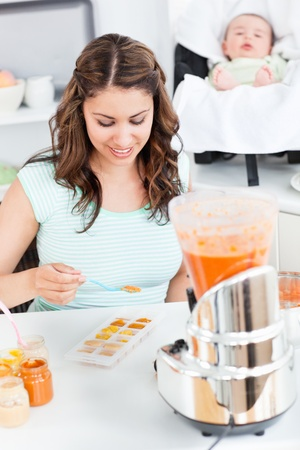 Caring mother preparing food for her lovely baby in the kitchen Stock Photo - 10173209