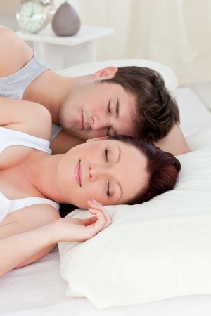 Young caucasian couple sleeping in bed photo