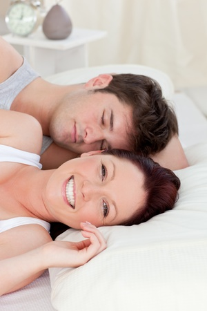 Smiling caucasian couple lying on bed photo