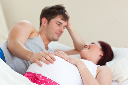 Joyful pregnant woman lying on bed with her husband photo