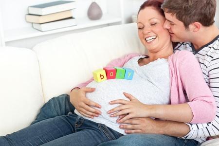 echtgenoot: Portret van een vrolijke zwangere vrouw met baby blokjes op haar buik en haar man kuste haar Stockfoto