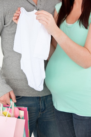 paternity: Close-up of a pregnant woman holding baby cloth and of her husband holding shopping bags