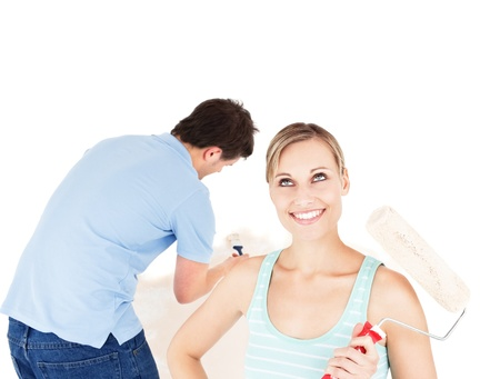 Positive couple painting a room