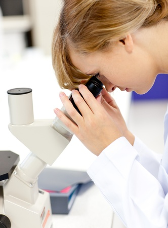 Concentrated female scientist looking through a microscope Stock Photo - 10172346