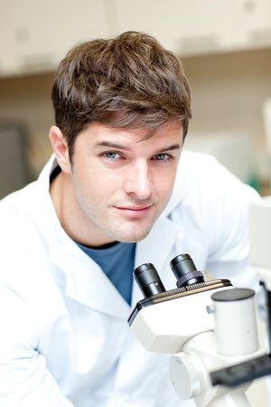 Handsome male scientist using a microscope Stock Photo - 10173002