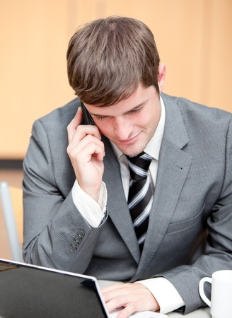 Concentrated businessman using his laptop while talking on phone photo