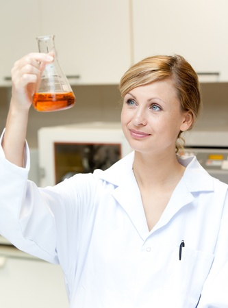 Portrait of a bright female scientist looking at an erlenmeyer Stock Photo - 10163703